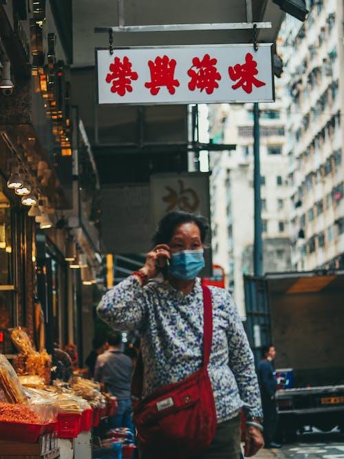 Anonymous ethnic woman walking along street during coronavirus