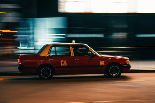 Vintage taxi car driving on street at night