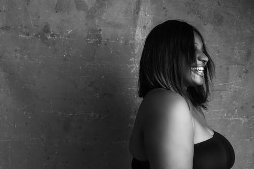Plump black woman with bare shoulders smiling brightly