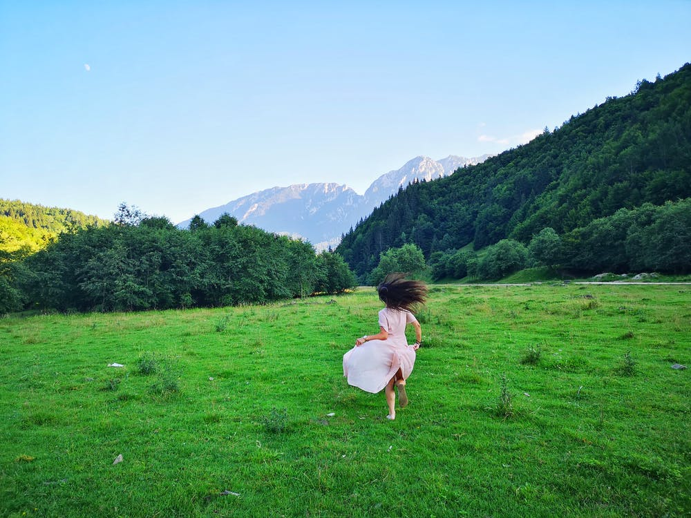 Woman running on grassy meadow in mountainous valley