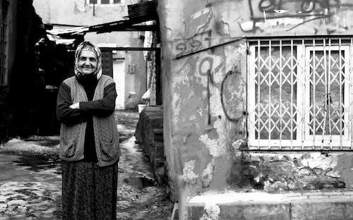 Woman in Black Coat Standing Beside Wall