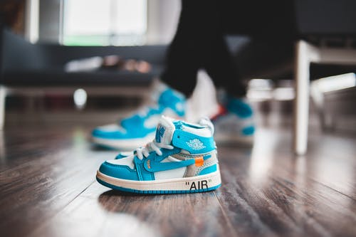 Tiny vibrant sneakers for baby on wooden floor in bright room in daylight on blurred background
