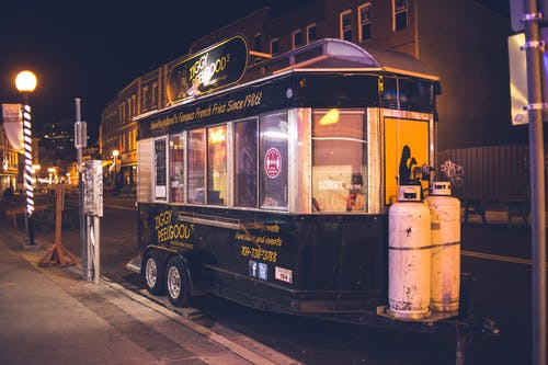 Big black food truck on small wheels with signboard and inscriptions on wall in downtown in light of lamps at night