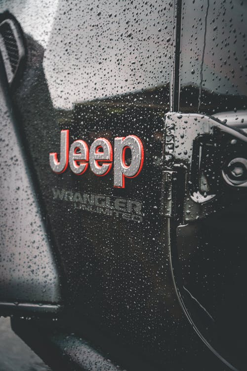 Metallic letters on wet surface of automobile covered with small transparent droplets of rain in daylight
