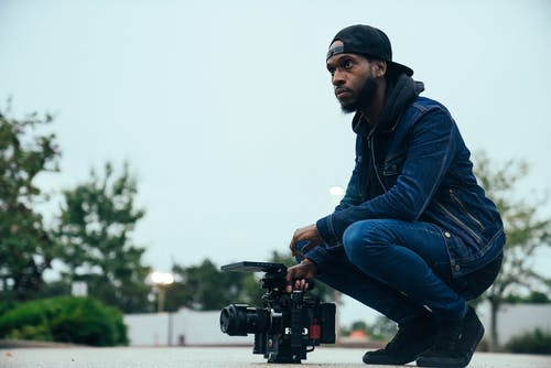 Man in Blue Denim Jeans and Jacket Holding a Video Camera