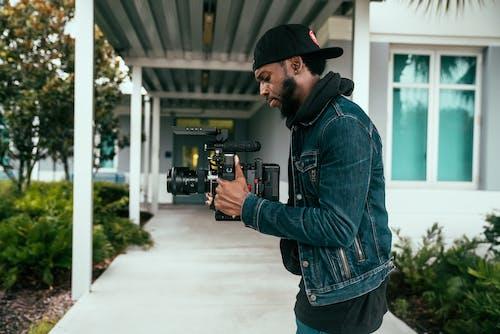 Man in Blue Denim Jacket Holding Black Video Camera