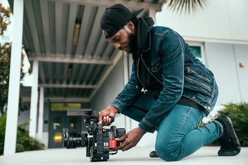 Man In Denim Jacket Holding a Video Camera