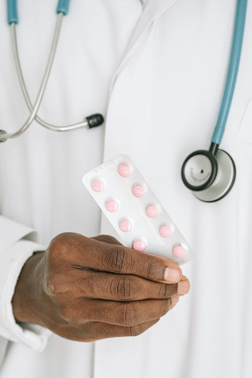 Person Holding White and Red Medication Pill