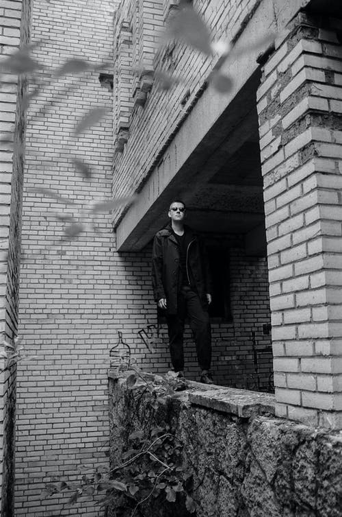 Stylish man standing on concrete structure near  old building