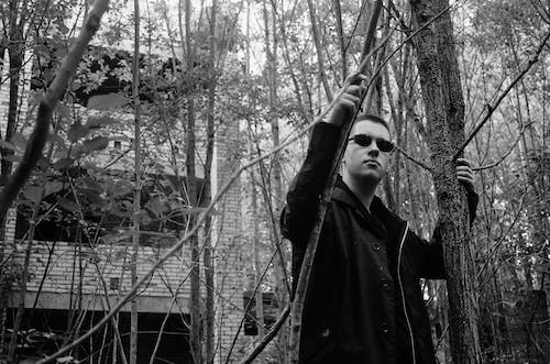 Low angle black and white of serious male in sunglasses holding trees while standing in park against brick building