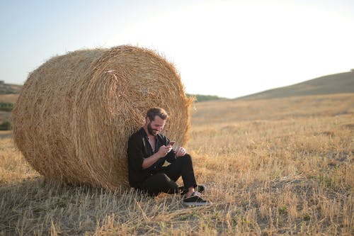 Man in Black Shirt Sitting on Brown Grass Field
