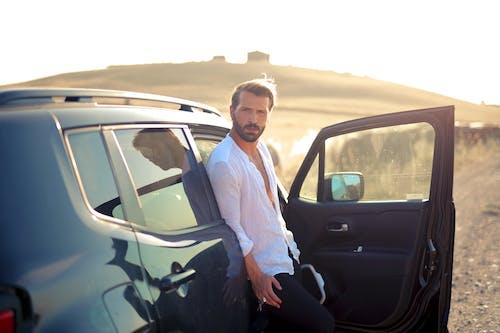 Man in White Dress Shirt and Black Pants Sitting on Black Car