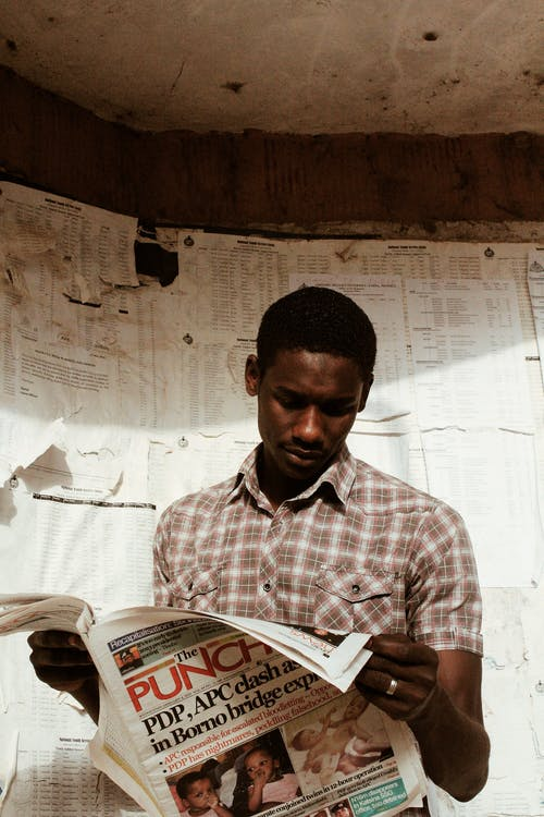 Pensive black man with newspaper in hands
