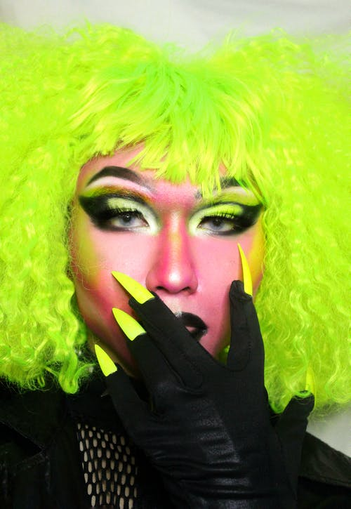 Artistic person with neon makeup and wig covering face with hand with long nails and looking at camera