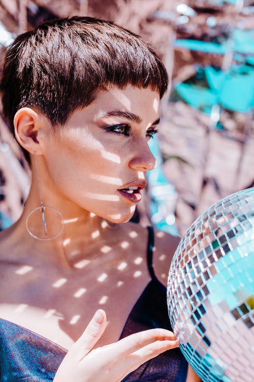 Charming female with bright glitter from silver disco ball looking into distance while standing on foil background