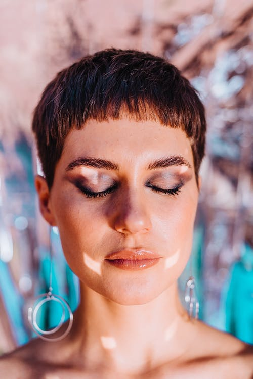 Calm woman with bright glitter on face