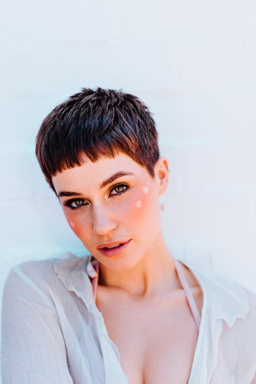 Attractive female with short hair and bright makeup with hearts on cheeks looking at camera while standing on white background