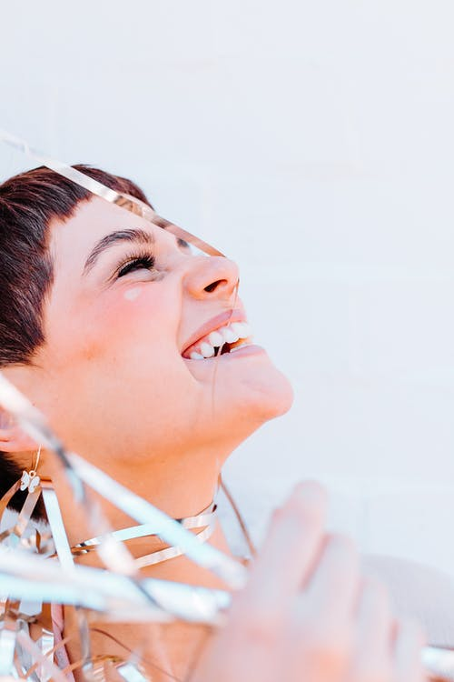 Crop positive female with closed eyes covered with decorative foil tinsel while standing on white background with head thrown back