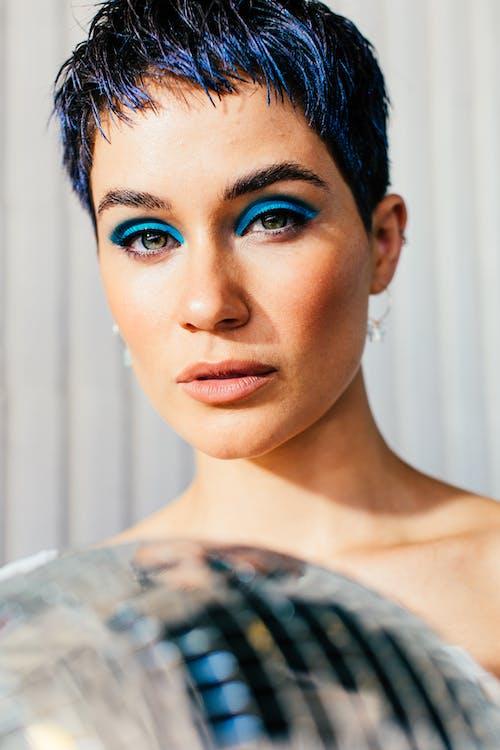 Gentle woman with blue eyeshadow on eyelids