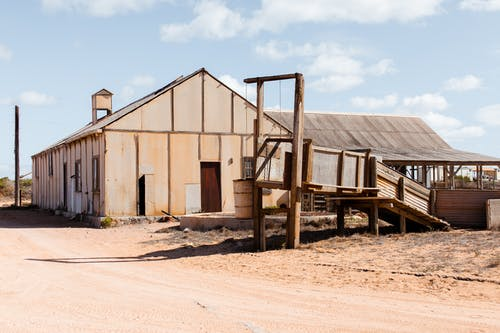 Aged countryside warehouse exteriors against empty roadway under blue cloudy sky on sunny day
