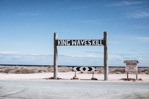 Inscriptions and road sign against sea in daytime