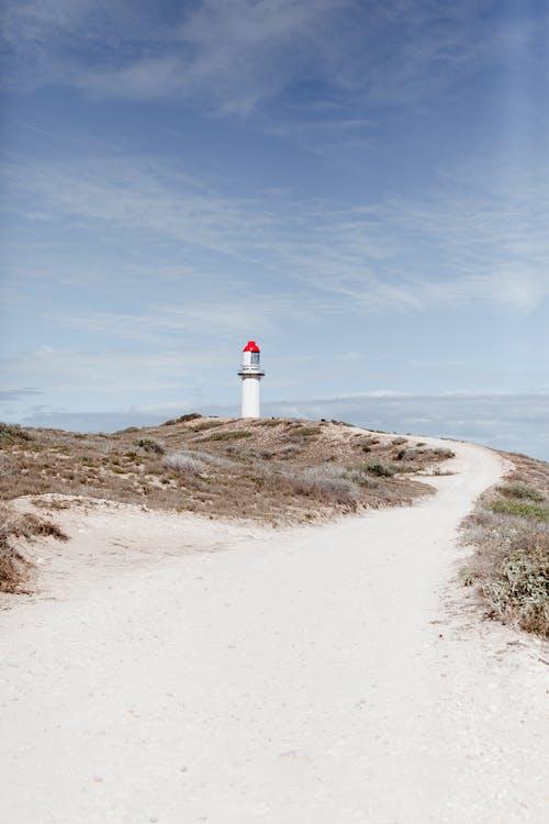 Lighthouse on shore against sea under cloudy sky