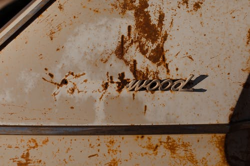 Corroded stains on part of old automobile with fragment of brand name written by metal letters