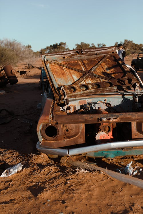 Rusty crushed automobile with damaged details located in desert with dry plants in hot day