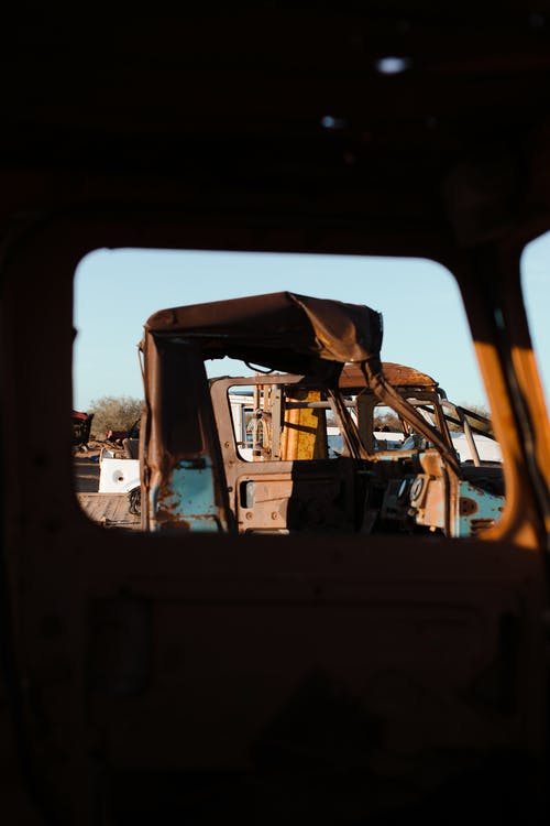 View from old auto on abandoned rusty damaged cars in sandy area in daytime standing in row