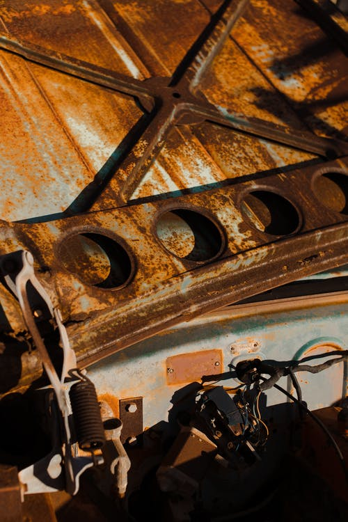 Inner surface of old car hood in corrosion and details in rusty stains