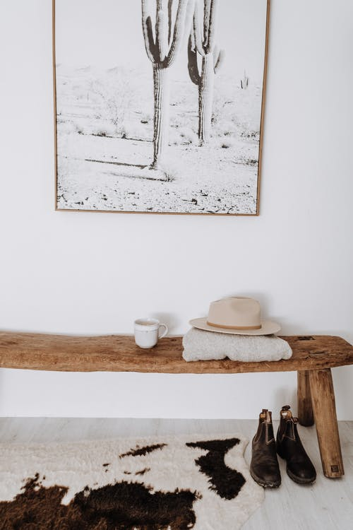 Wooden bench with hat placed in light corridor with carpet and picture in apartment in light minimalistic style