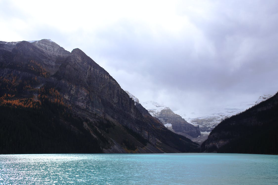 Picturesque landscape of blue water surface of pond surrounded by rocky mountainous terrain under cloudy sky