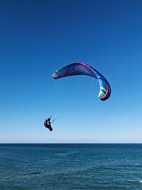 Paraglider flying over blue sea water