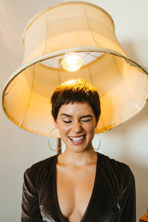 Positive female with short hair wearing decollete dress making funny face under floor lamp