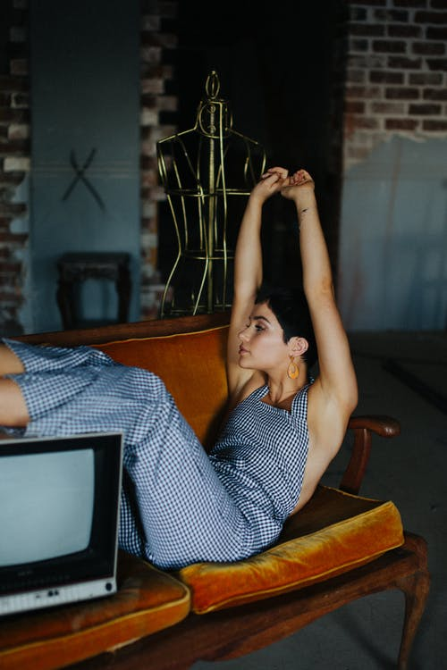 Side view of female with hands up sitting on wooden sofa with legs on vintage TV set in tailor workshop