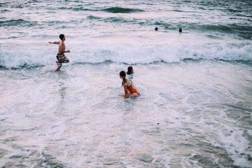 High angle of travelers running and swimming in foamy waves of sea in tropics