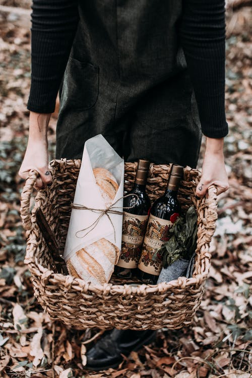 Person carrying basket with fresh bread and wine