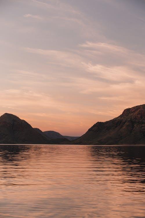 Sunset sky over rippling lake in mountainous terrain