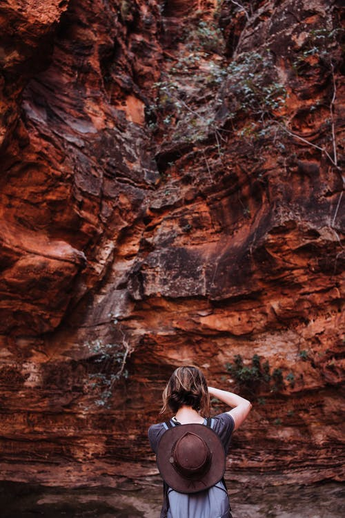 Back view of unrecognizable female tourist taking picture of rough stony cliff in highlands