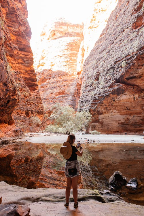Unrecognizable woman taking picture on phone of canyon near water