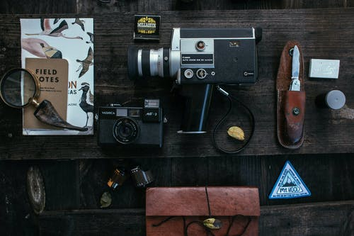 Overhead of vintage cameras near camera roll and knife near book about birds and lens placed on wooden table
