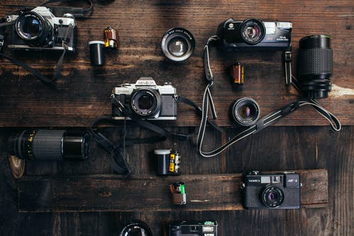 Overhead of retro photo cameras near various lenses and films on wooden surface