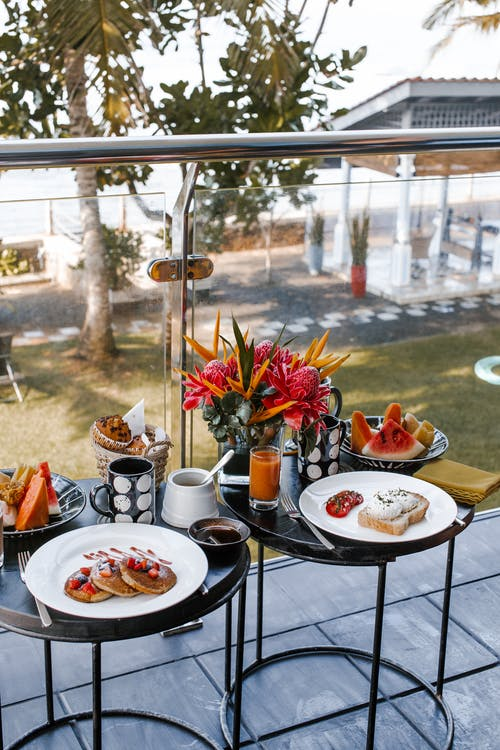 Round tables on balcony with pancakes with berries near plate with sandwich with poached eggs and tomatoes and plates with different fruits near mugs with drink and vase with flowers