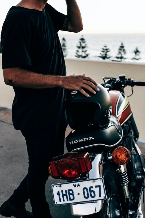 Side view of anonymous ethnic male biker wearing black clothes standing near modern motorbike with helmet on street near concrete fence