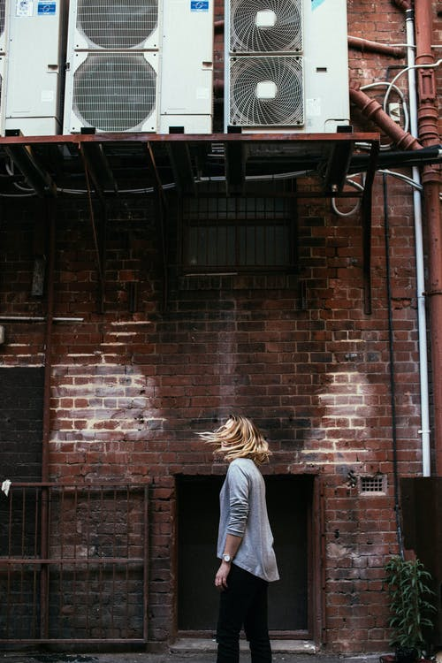 Side view of unrecognizable female with flying hair standing on street near aged house with air conditioning units in city