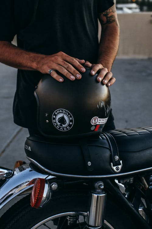 Unrecognizable tattooed ethnic male standing near modern motorcycle with hands on black helmet on sidewalk in street against concrete fence