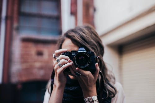 Unrecognizable female photographer taking photo and covering face with camera while standing on street against brick building on blurred background
