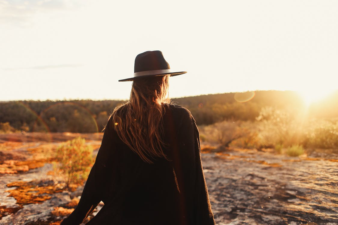 Back view of anonymous female in black headwear standing on rocky ground against coniferous forest during sunset time in nature