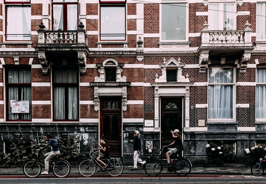 Full body side view of cyclists on bicycles riding along aged house with brick wall doors and balconies on street