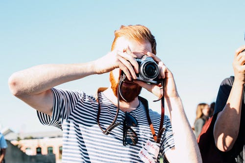 Unrecognizable redhead bearded male photographer in casual outfit concentrating on taking picture by vintage photo camera on street event at daytime